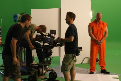 Behind the scenes. Alex at camera on a greenscreen shoot